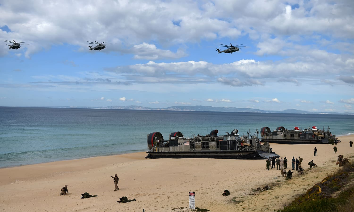US navy helicopters fly over as US marines prepare to disembark from the hovercrafts deployed by the USS Arlington amphibious transport dock. — AFP