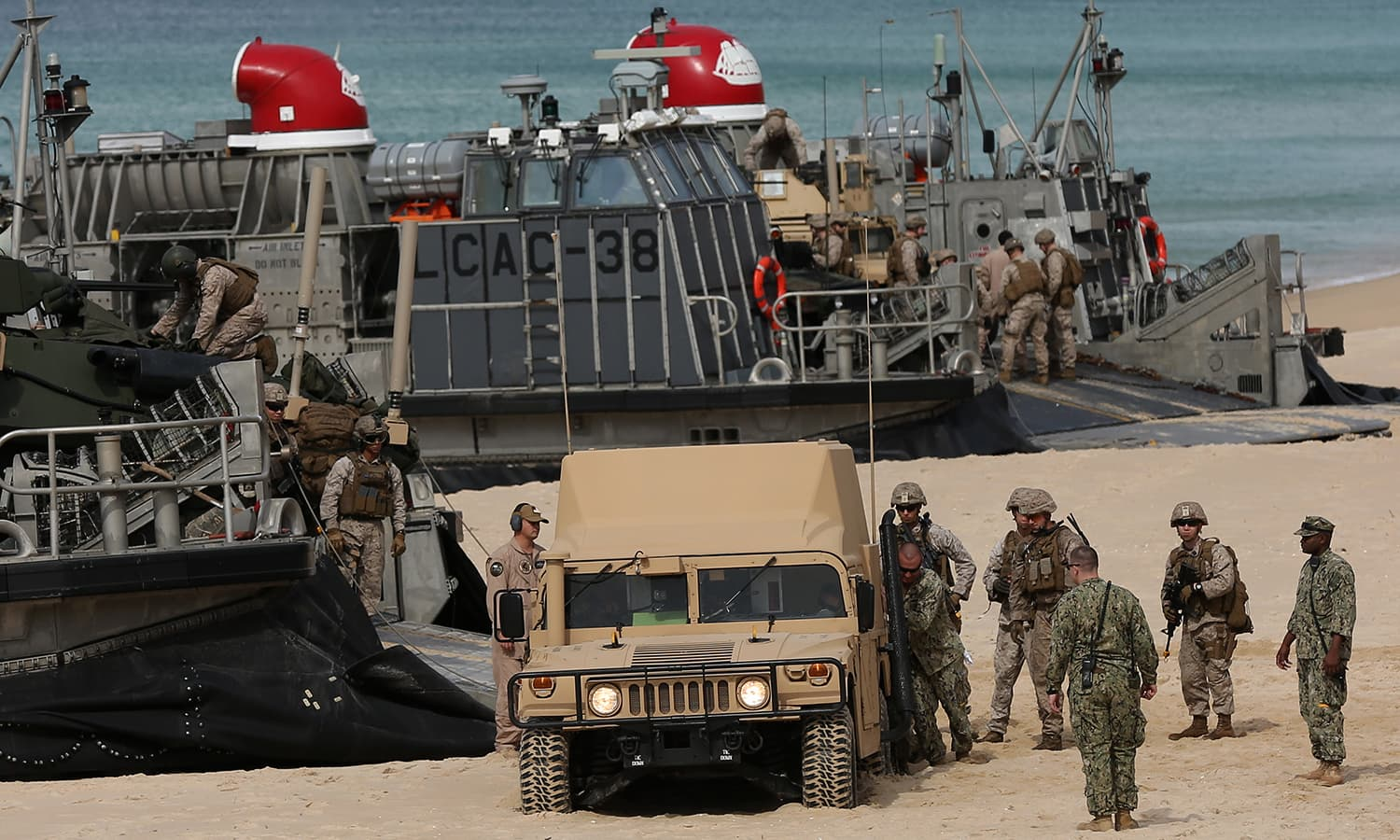 US marines try to free an armoured vehicle from the sand after it sunk while getting off a US Navy hovercraft after landing at the beach. — AP