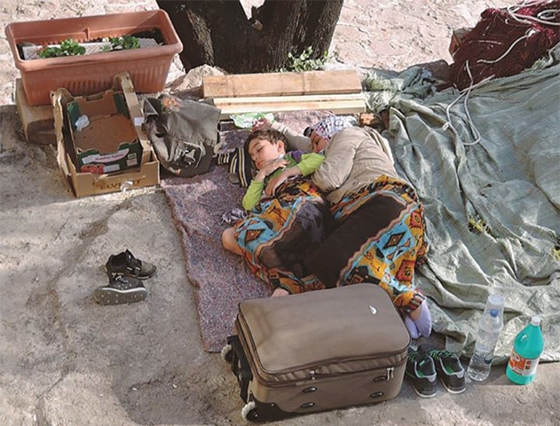 Exhausted and tired, refugees sleep with whatever little belongings they have