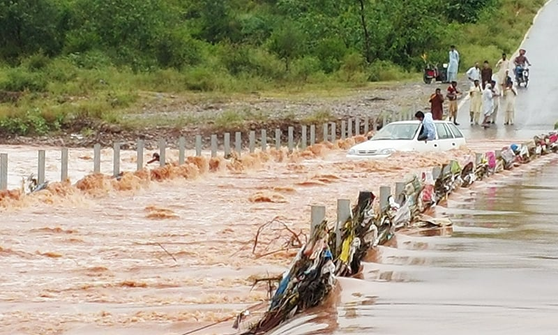 A car is stuck on a poorly planned bridge during flooding - Dawn.com