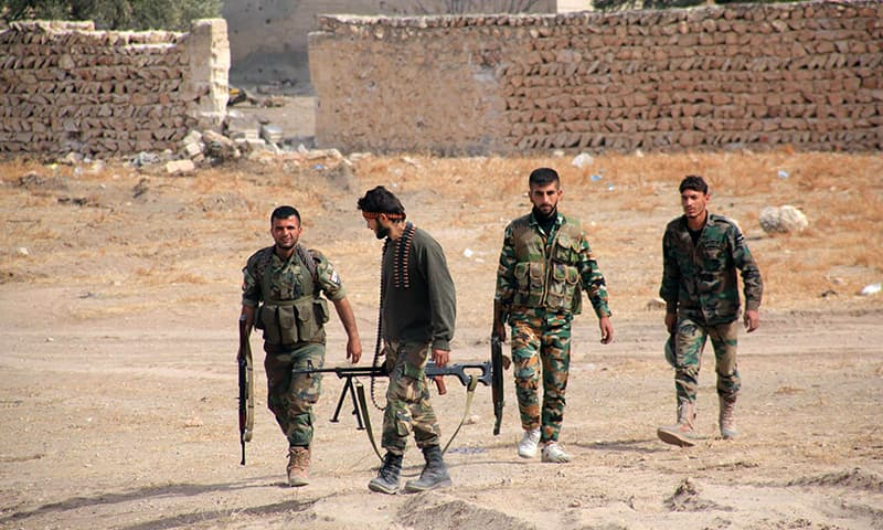 Syrian regime soldiers walk in an area in the eastern outskirts of the northern Syrian city of Aleppo. —AFP