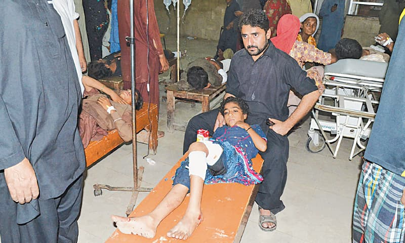 A GIRL injured in the blast lies on a bench in a hospital in Jacobabad.—Reuters