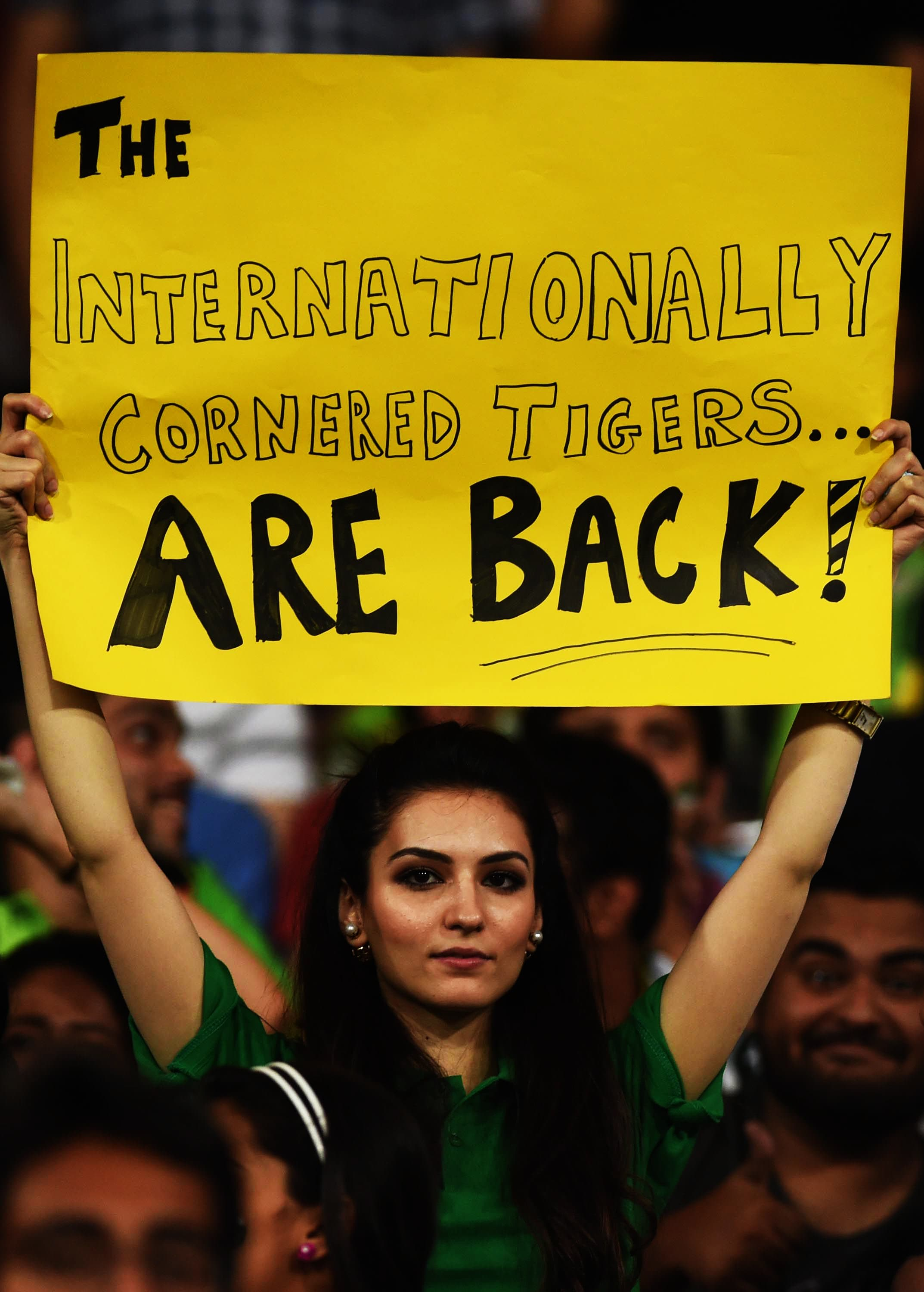 A fan holds aloft a banner during the T20 match between Pakistan and Zimbabwe at the Gaddafi Stadium in Lahore on May 24, 2015. — AFP