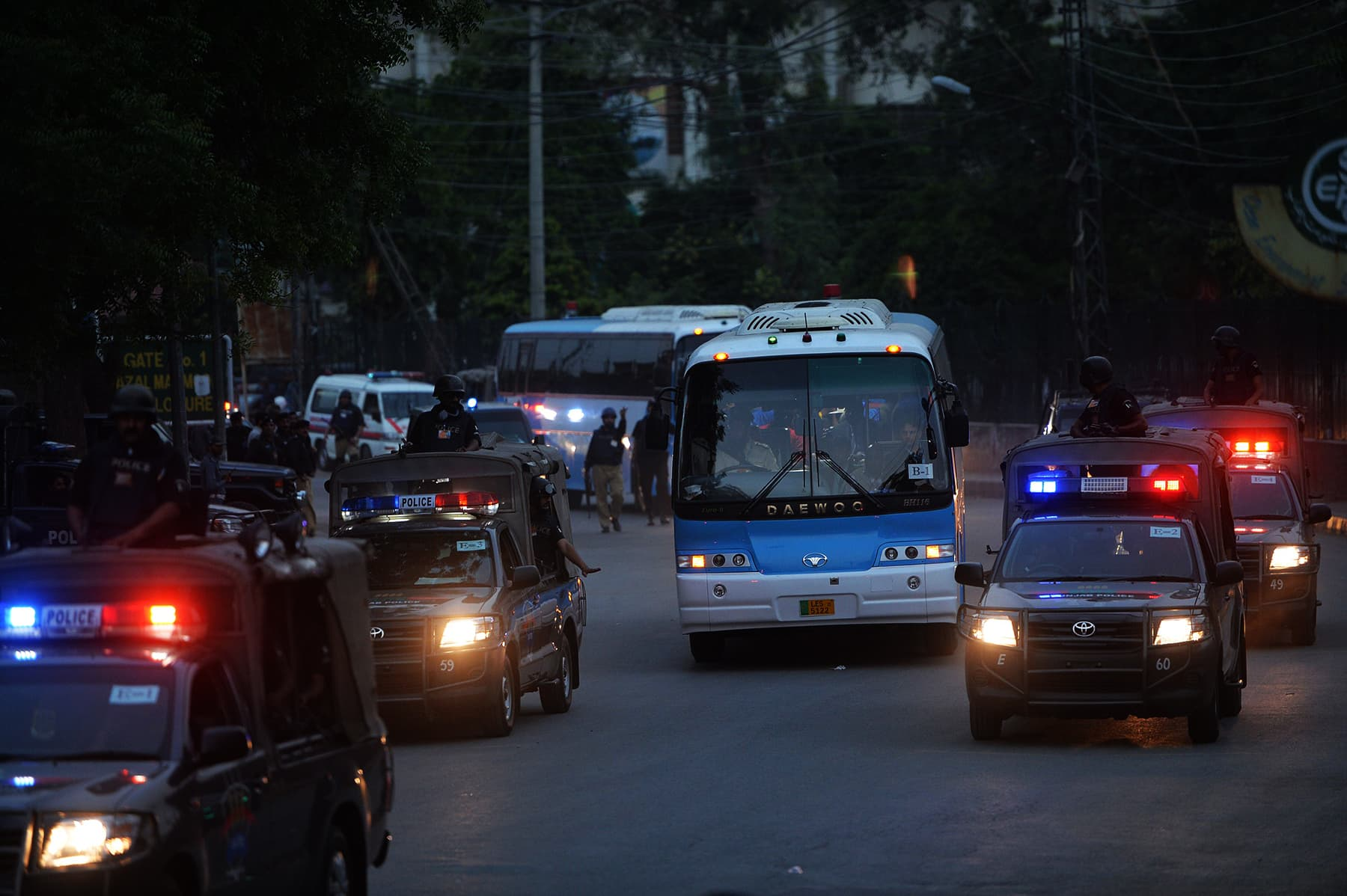 Security personnel escort buses carrying the Zimbabwe and Pakistan cricket teams as they leave a practice session at the Gaddafi Cricket Stadium in Lahore on May 19, 2015. — AFP