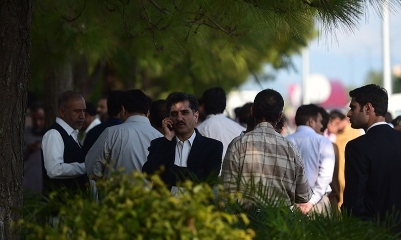 Federal employees gather outside their offices after a 7.5-magnitude earthquake in Islamabad. -AFP