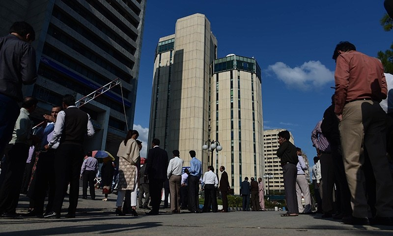 Pakistani federal employees gather outside their offices after a 7.5-magnitude earthquake. -AFP