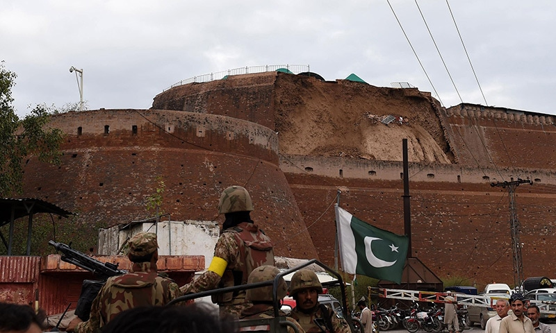 Pakistani Army soldiers observe the damaged wall of a fort used by security forces after an earthquake in Peshawar. -AFP