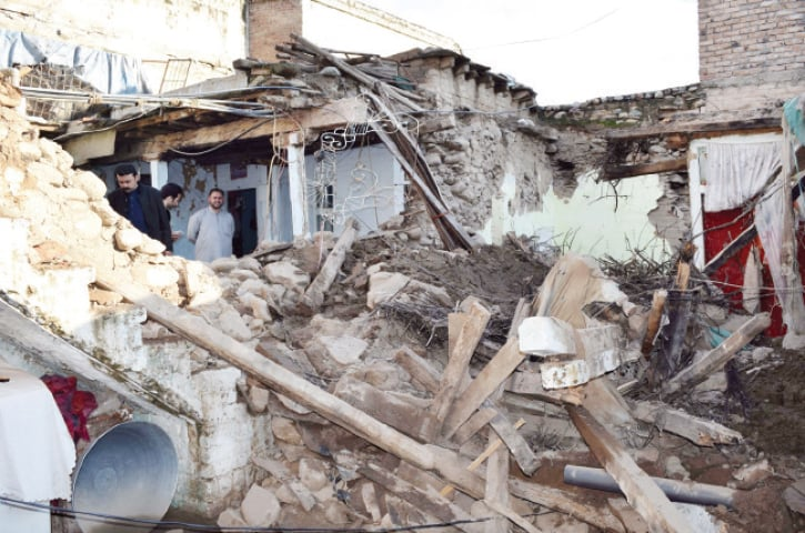 People watch the rubble of a house that was destroyed after the earthquake struck Mingora on Monday. — Dawn