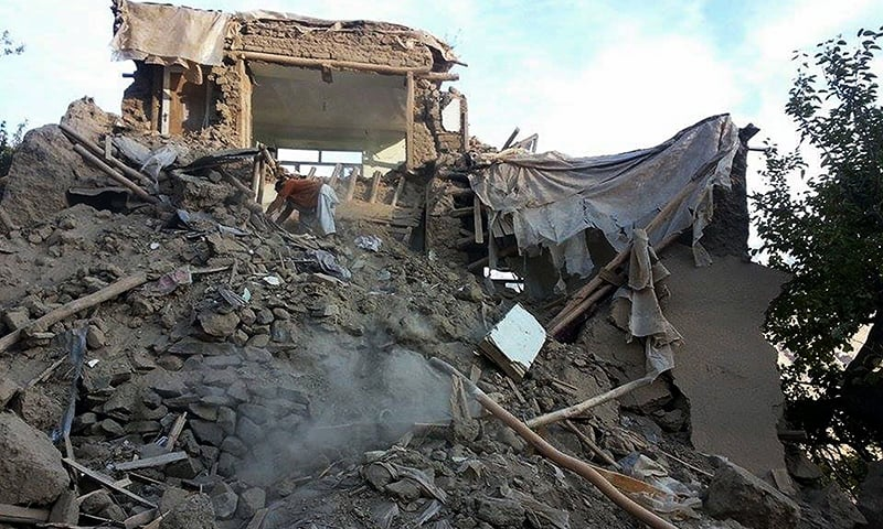 An Afghan man digs through the rubble of a damaged building after a powerful earthquake in Raman Kheel village in Panjshir valley on October 26, 2015. —AFP