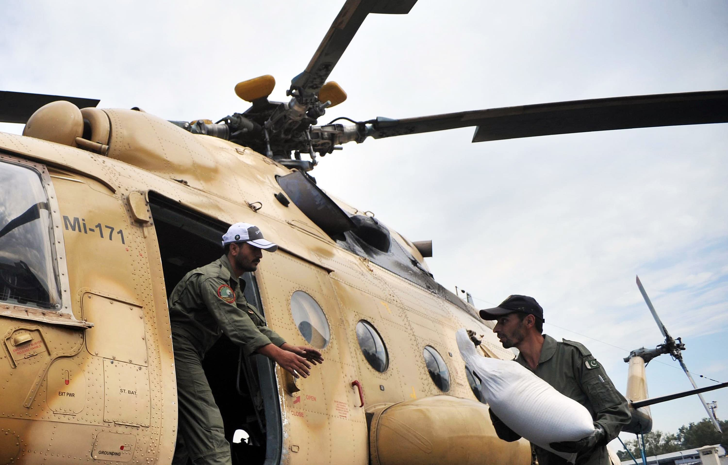 Pakistani soldiers load food bags for earthquake survivors into an army helicopter in Peshawar on October 27, 2015. —AFP