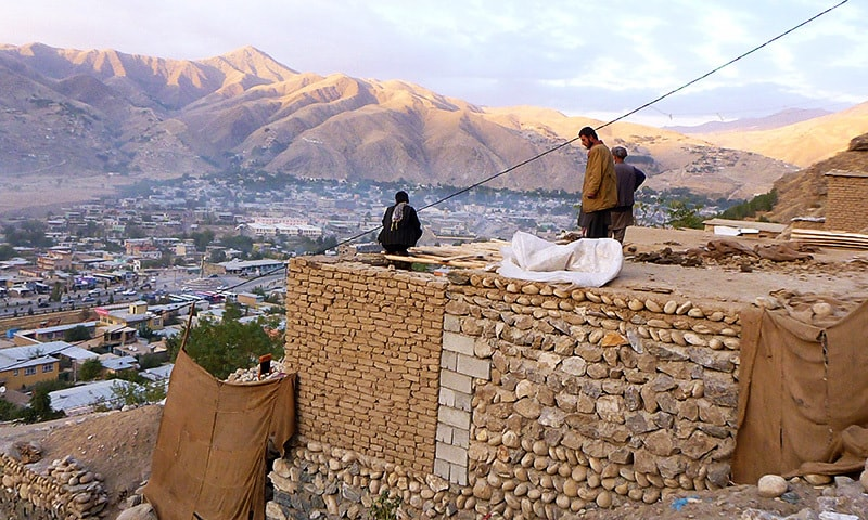 In this photograph taken on October 26, 2015, Afghan householders gather on the roof of a house Faizabad in Badakhshan Province after a powerful earthquake hit the Central Asian nation. —AFP
