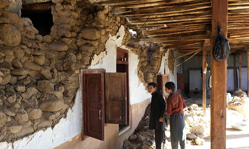 Young Pakistani children look at a damaged house following an earthquake in Lower Dir on October 27, 2015. —AFP