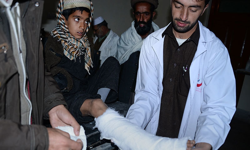 A paramedic (R) examines a young injured earthquake survivor at a hospital in quake-hit Shangla on October 28 ─ AFP