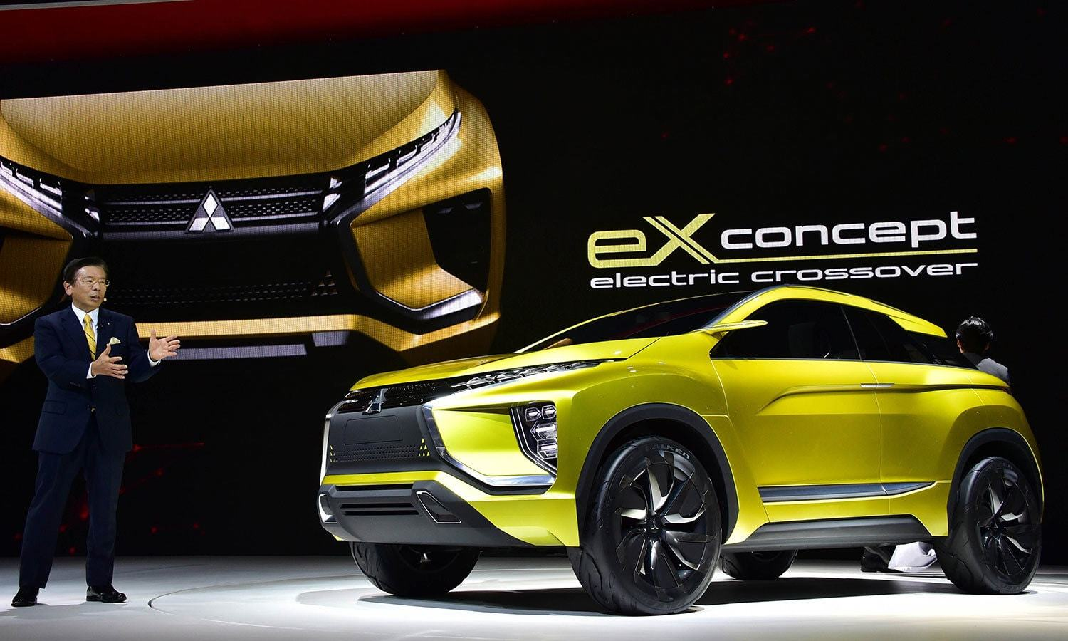 Mitsubishi Motors Corp's President Tetsuro Aikawa speaks next to its concept car eX concept electric crossover