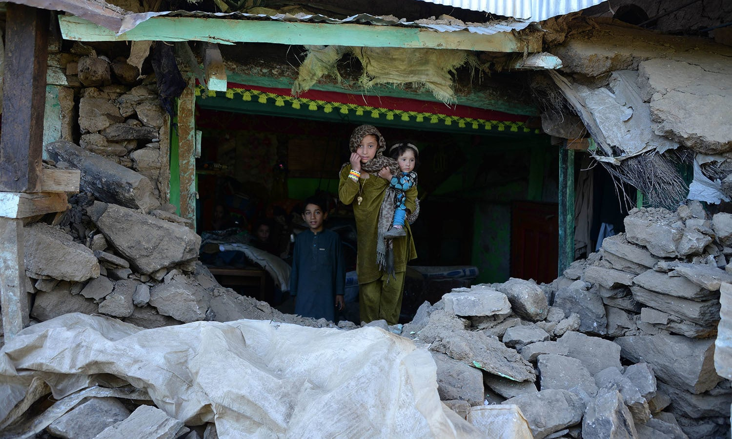 Earthquake survivors take refuge at a damaged house in the quake-hit Shangla district in Pakistan's Khyber Pakhtunkhwa province. — AFP