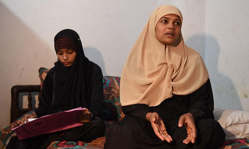 Razia Begum sits with her daughter Zoya Bibi during an interview in Karachi. —AFP