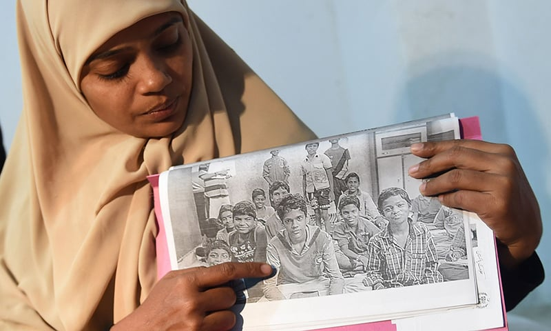 Razia Begum displays a picture of her son, Mohammad Ramazan during an interview in Karachi. —AFP