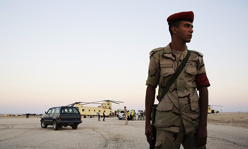 An Egyptian soldier stands guard as emergency workers unload bodies of victims from the crash of a Russian aircraft over the Sinai peninsula. -AP