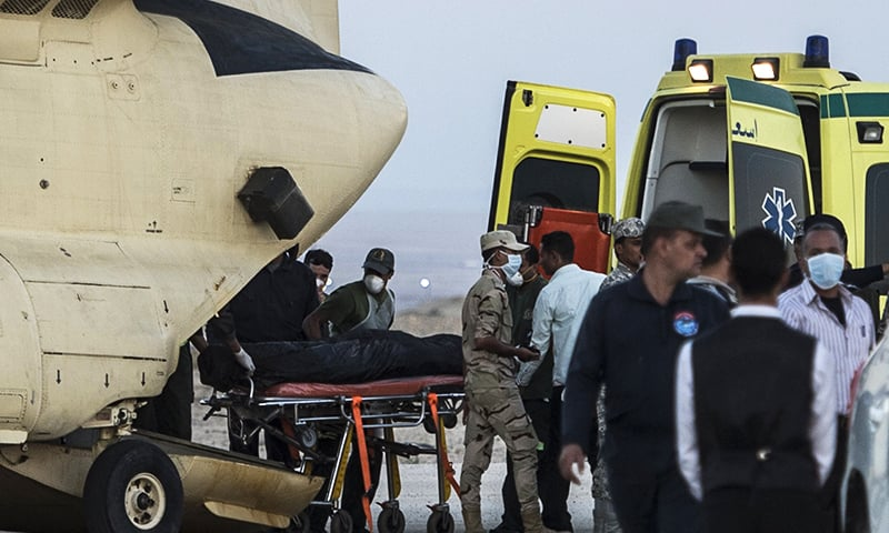 Egyptian paramedics load the corpses of Russian victims of a Russian passenger plane crash in the Sinai Peninsula, into a military aircraft at Kabret military air base. -AFP