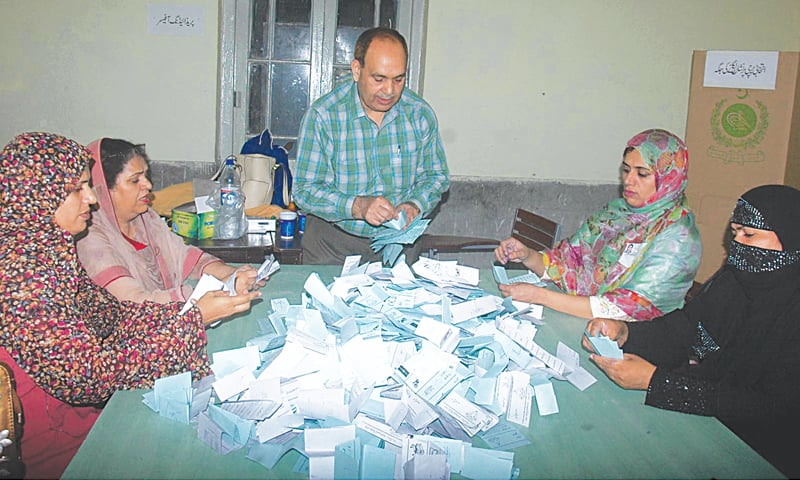 LAHORE: Election staff count votes at a polling station on Saturday.—INP