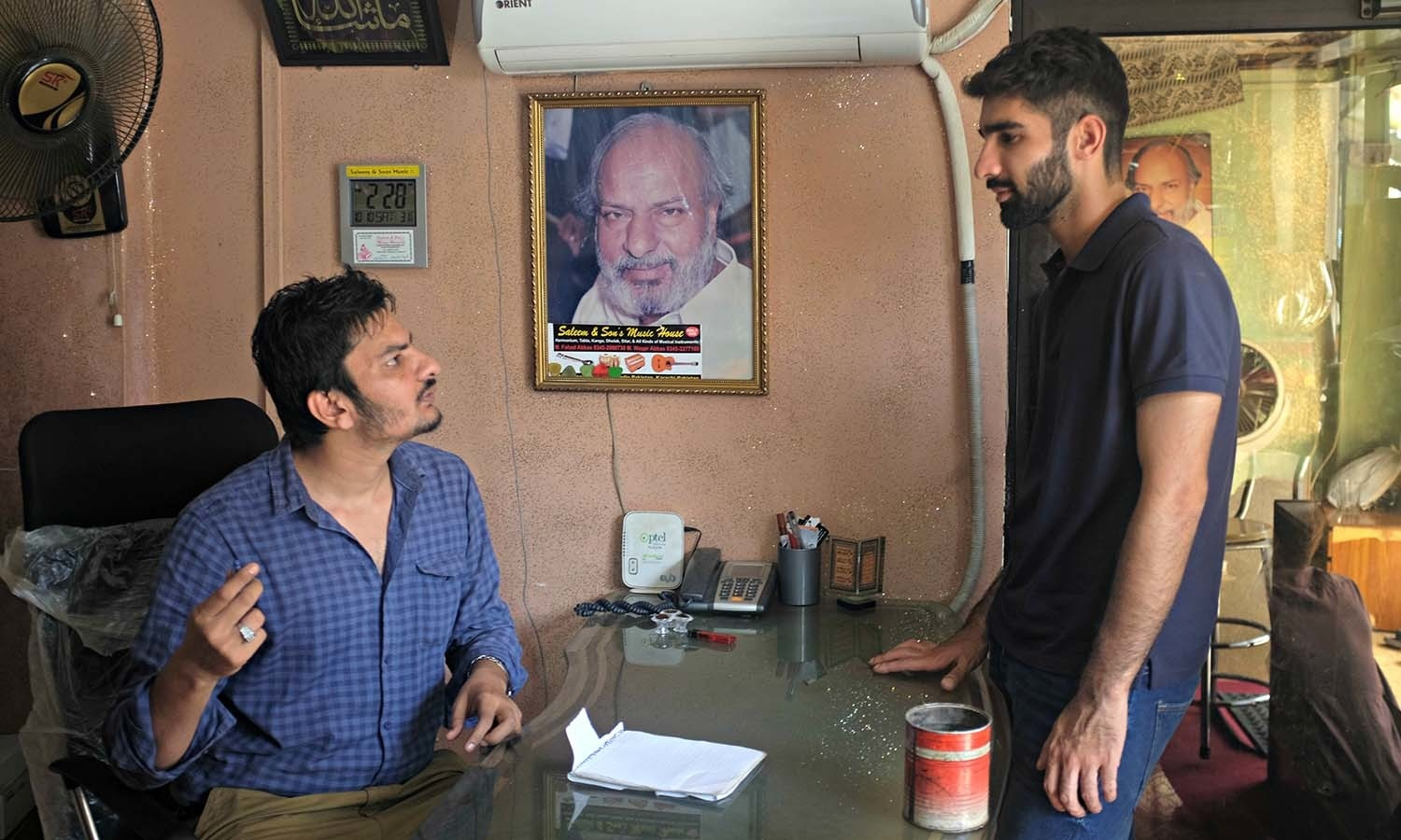 Waqar speaks to a customer in his office at 'Saleem and Sons Musical Store'.