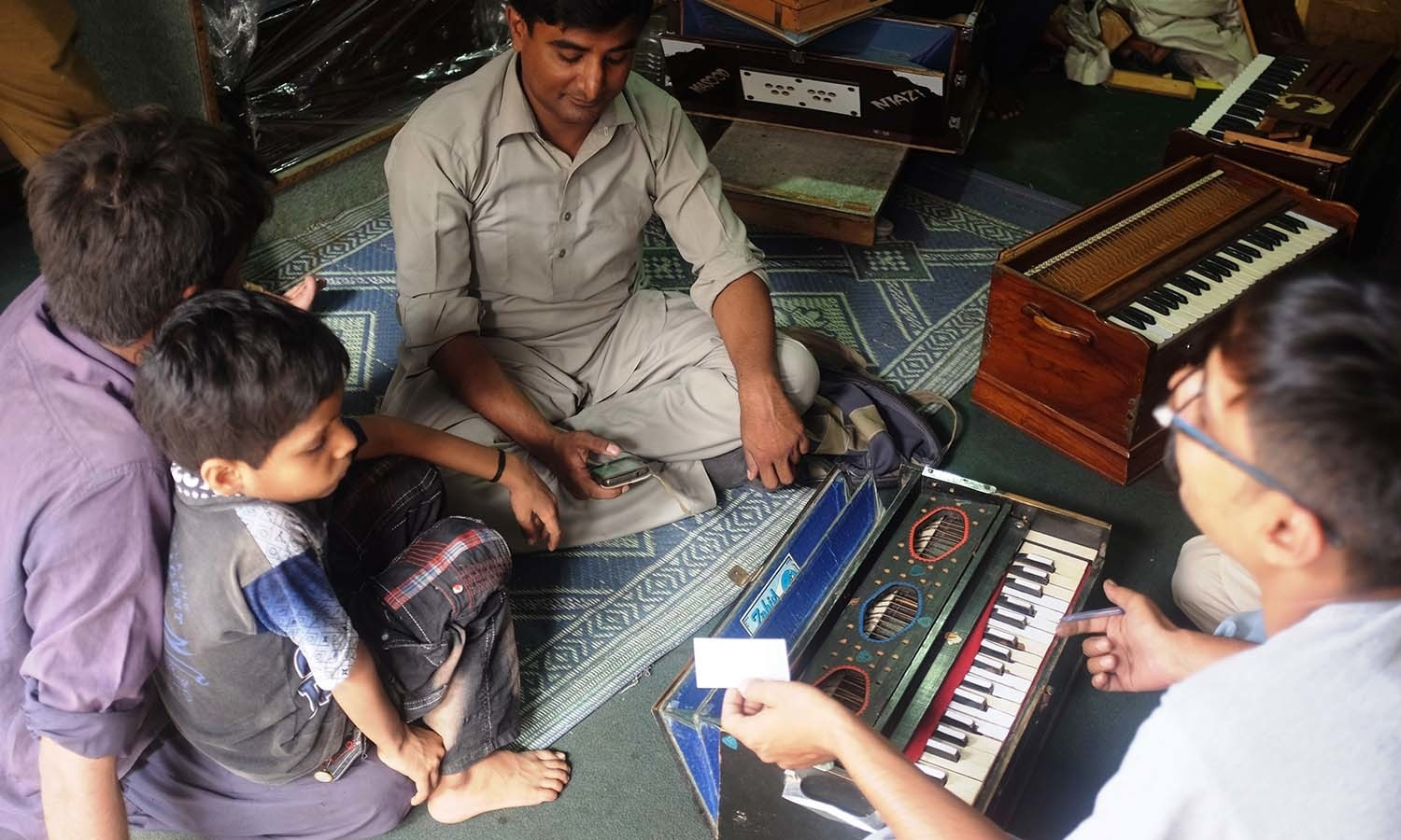 A musician from Hyderabad gets his harmonium repaired at Waqar's shop.