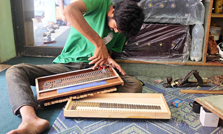 A worker repairs a harmonium.