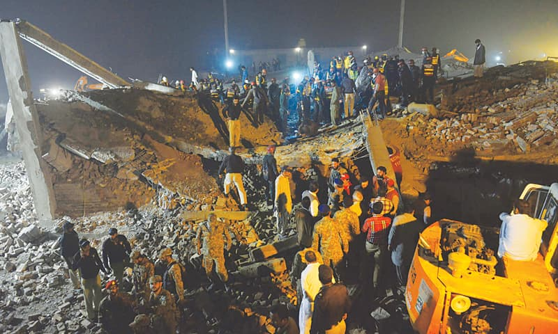 LAHORE: Rescuers search for victims in the rubble of a collapsed factory building on the outskirts of the city on Wednesday.—White Star