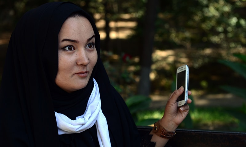 Afghan psychologist Fatima, 23, holds her phone during an interview with AFP at Wazir Akbar Khan Park in Kabul. — AFP