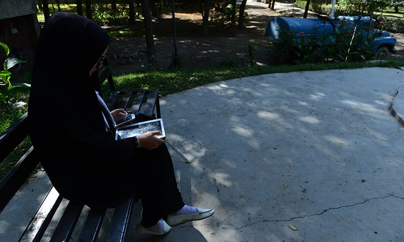 Afghan psychologist Fatima, 23, uses her tablet and phone during an interview with AFP at Wazir Akbar Khan Park in Kabul. — AFP