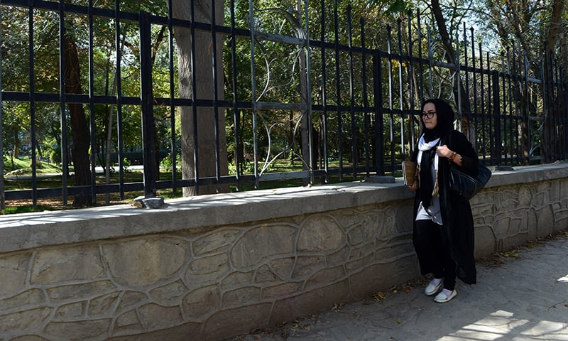 Fatima, 23, walks along the road next to the Wazir Akbar Khan Park in Kabul. — AFP