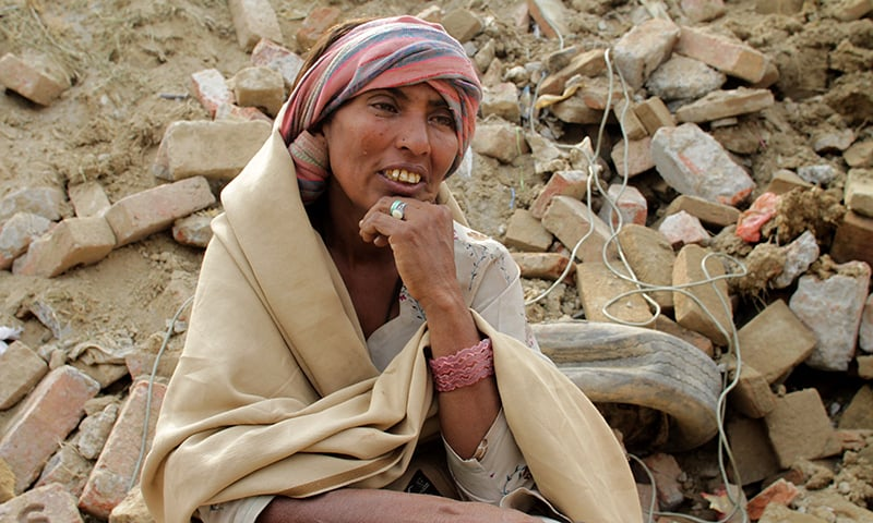 A woman sits on debris of a collapsed building waiting for her missing son to be evacuated. —AP