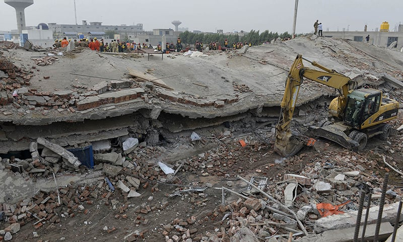 Rescuers search for victims in the rubble of the collapsed factory. —AFP