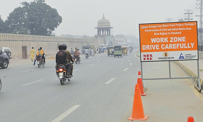 A sign placed on a road near the Shalamar Gardens reads 'Work Zone Drive Carefully'. The route is part of the Lahore Orange Metro Train Project that has become controversial as it is passing along historical heritage sites.—Arif Ali / White Star