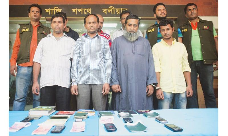 DHAKA: Bangladesh police escort suspected militants, including four Pakistani nationals, on Saturday.—AFP