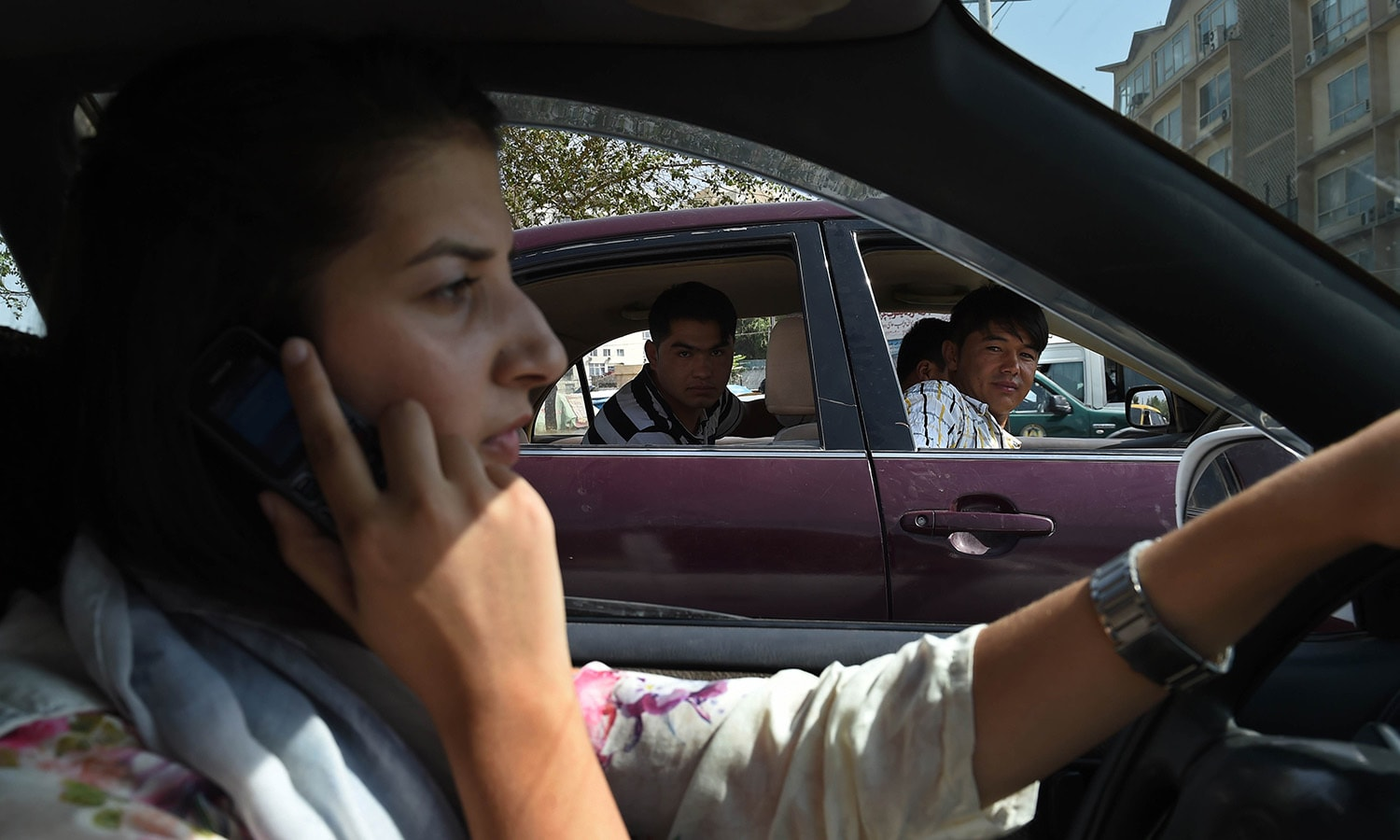 In this photograph taken on September 4, 2015,  Afghan woman, Rokhsar Azamee, 23, drives her car as Afghan youths stare at her in the streets of Kabul. — AFP