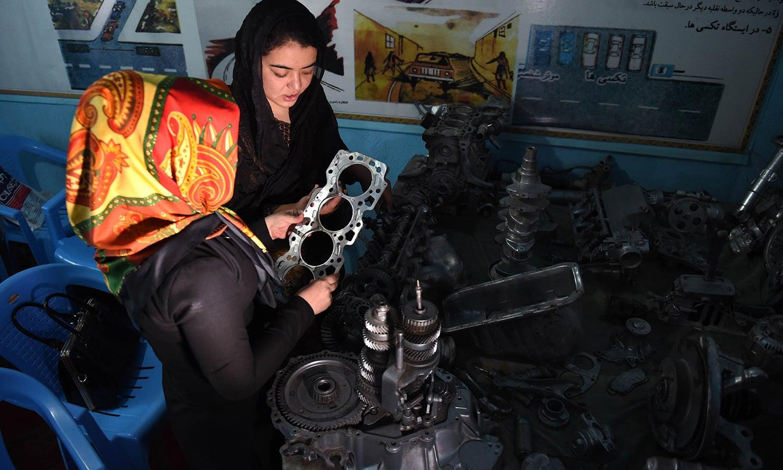 Suhaila Sama, 25, examines spare car parts during a lesson at the Haidari Driving School in Kabul. — AFP/file