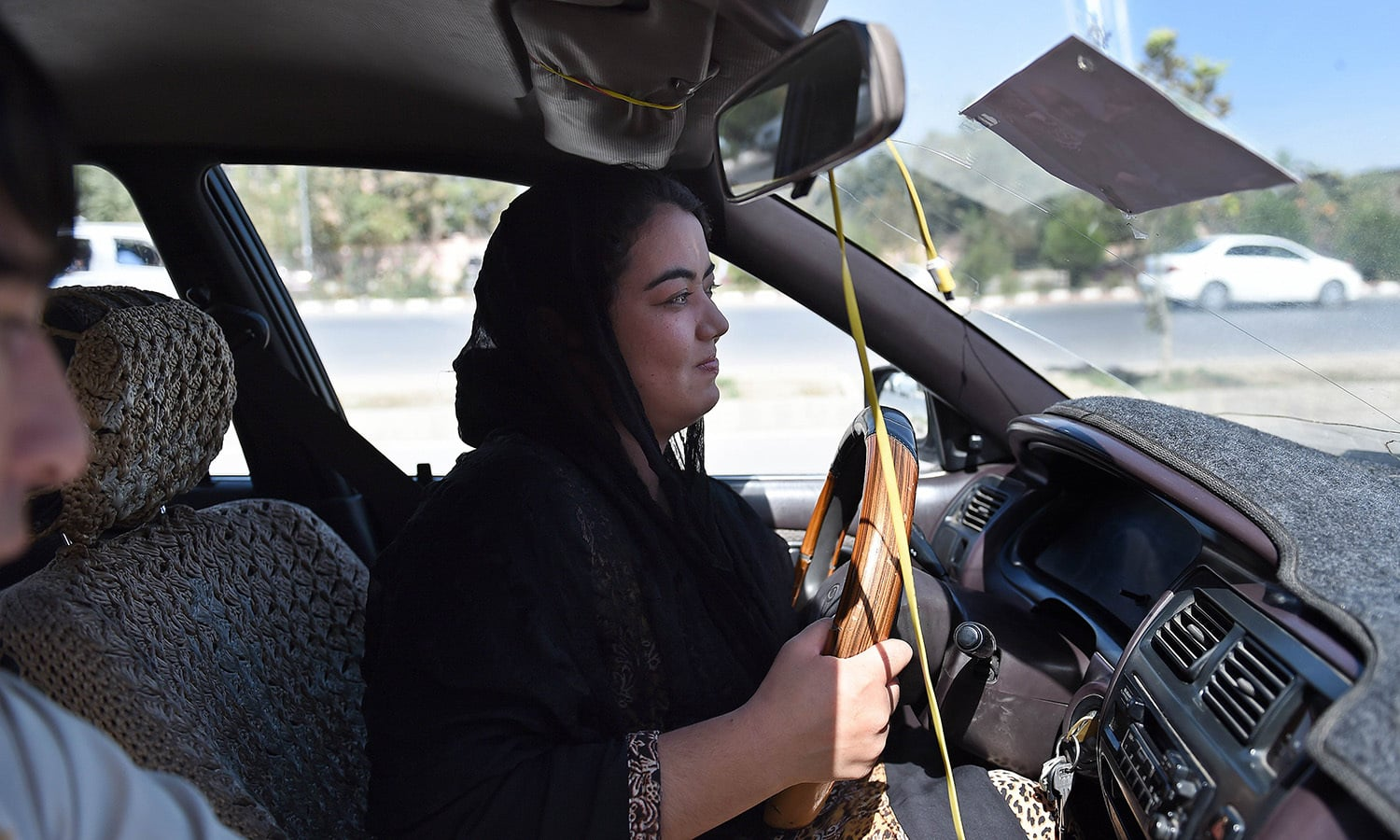Suhaila Sama, 25, drives during a practical lesson with a teacher from the Haidari Driving School along the streets of Kabul.  — AFP