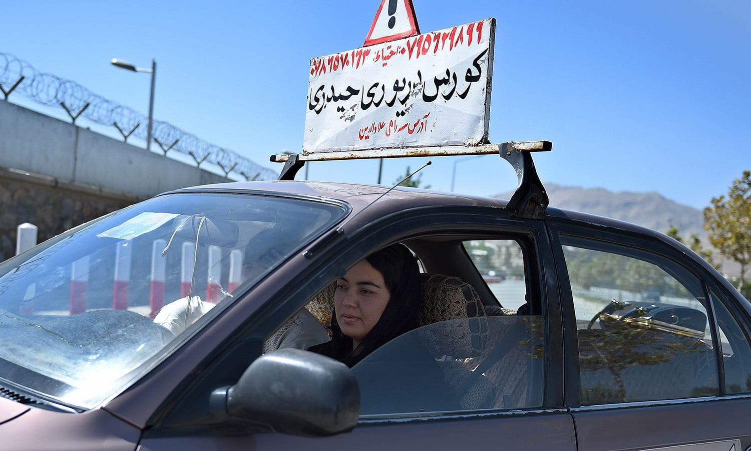 Suhaila Sama, 25, drives during a practical lesson with a teacher from the Haidari Driving School along the streets of Kabul.— AFP
