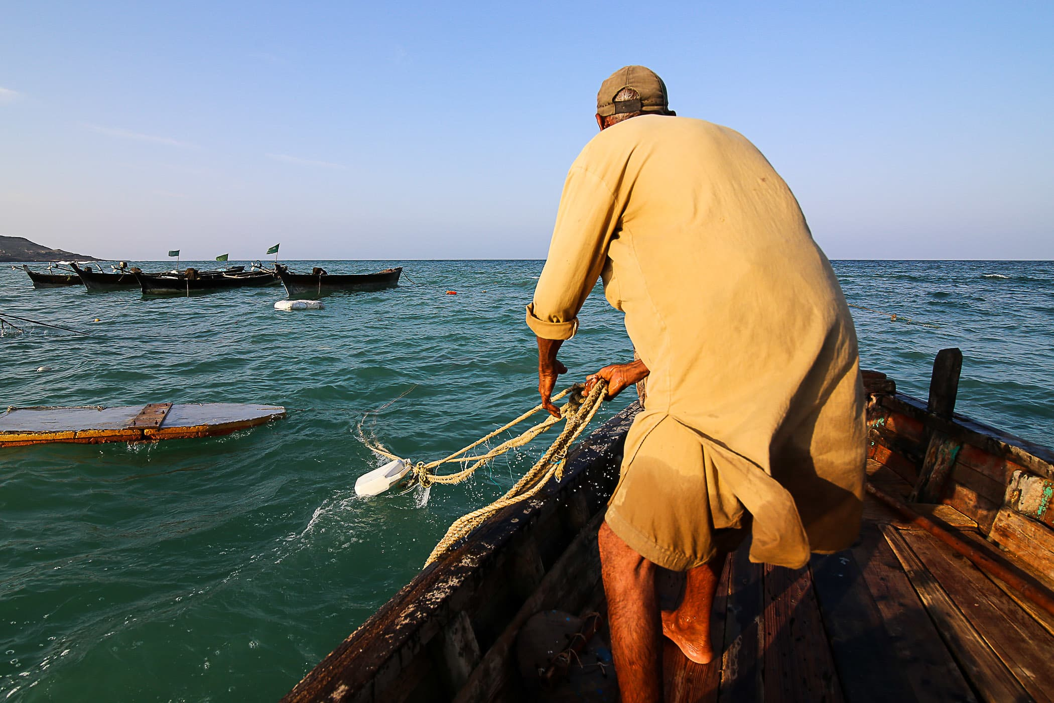 Chacha Majeed pulls a tethered line to reach the other boats.