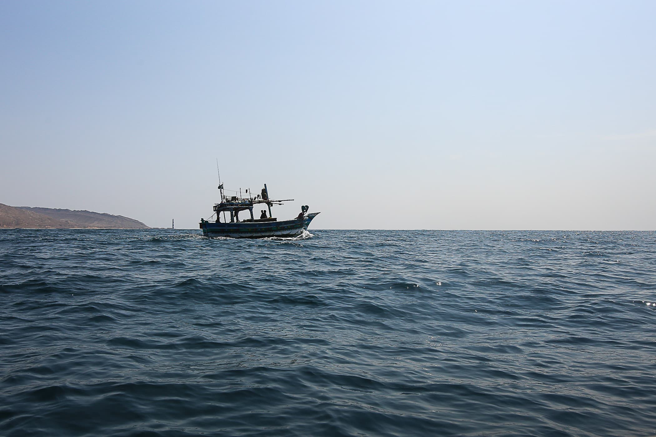A small trawler heads out into the ocean to fish.