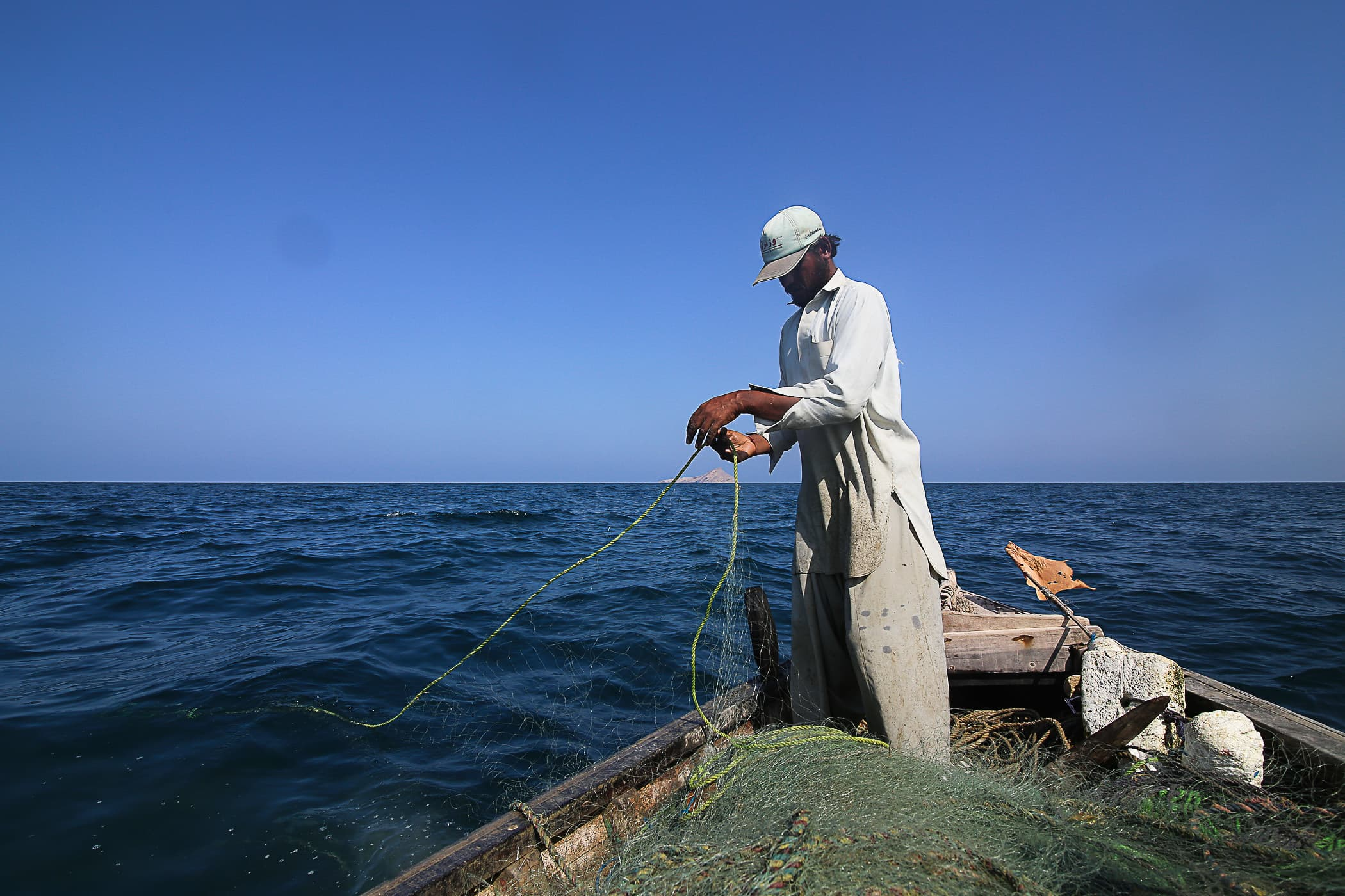 Qasim places the nets back into the sea.