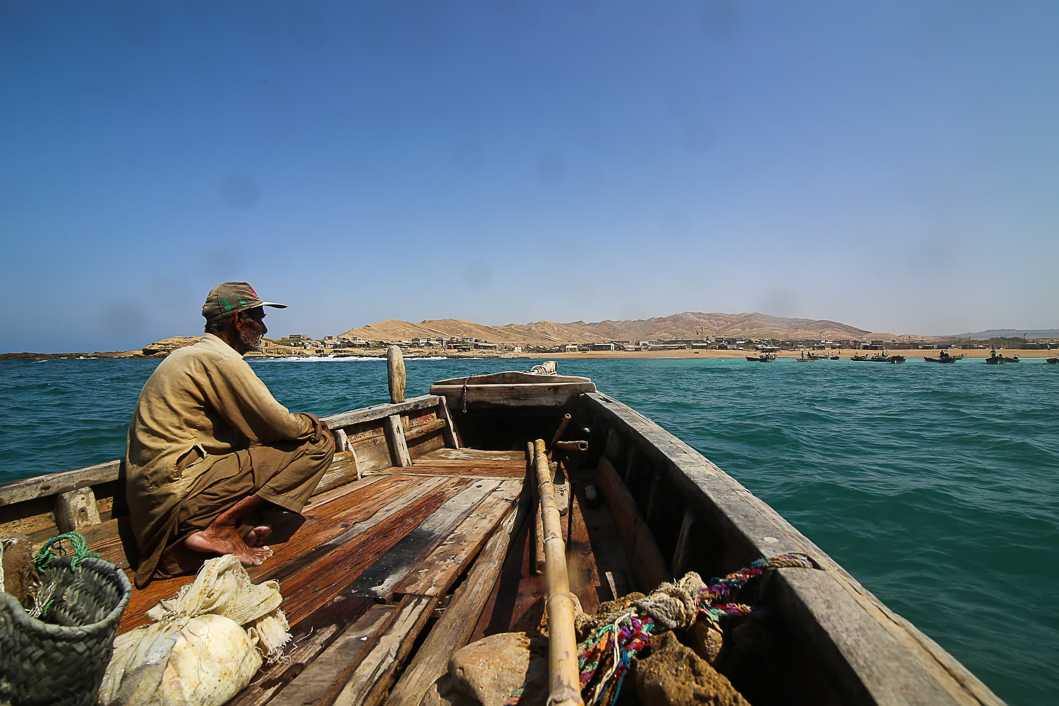 Chacha Majeed sits on the bow of the boat as the three of us head back to the sea shore at Mubarak Village.