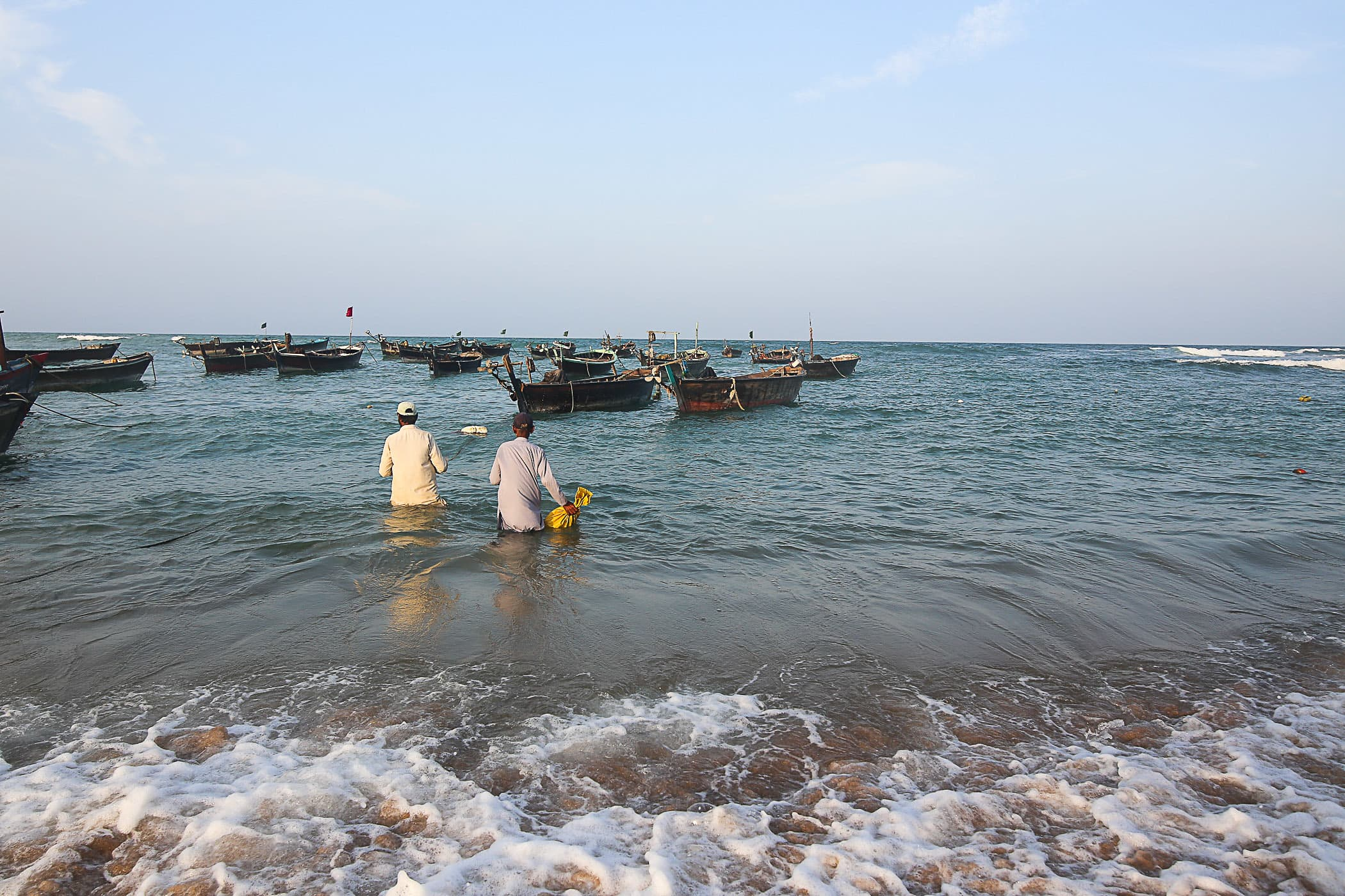 On the morning of the second day Chacha Majeed and Qasim wade into the water to get onto their boat.