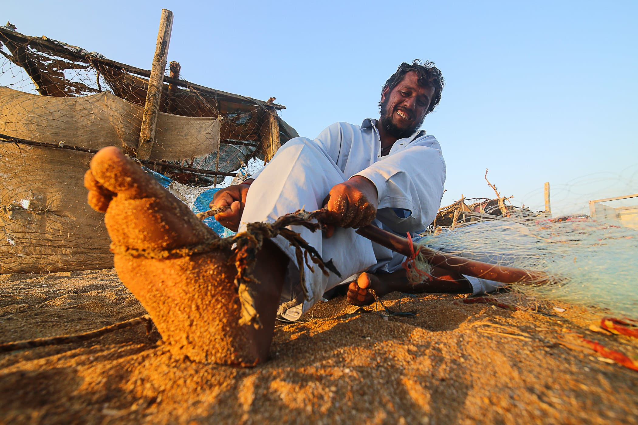 Qasim tightens a knot on his fishing net.