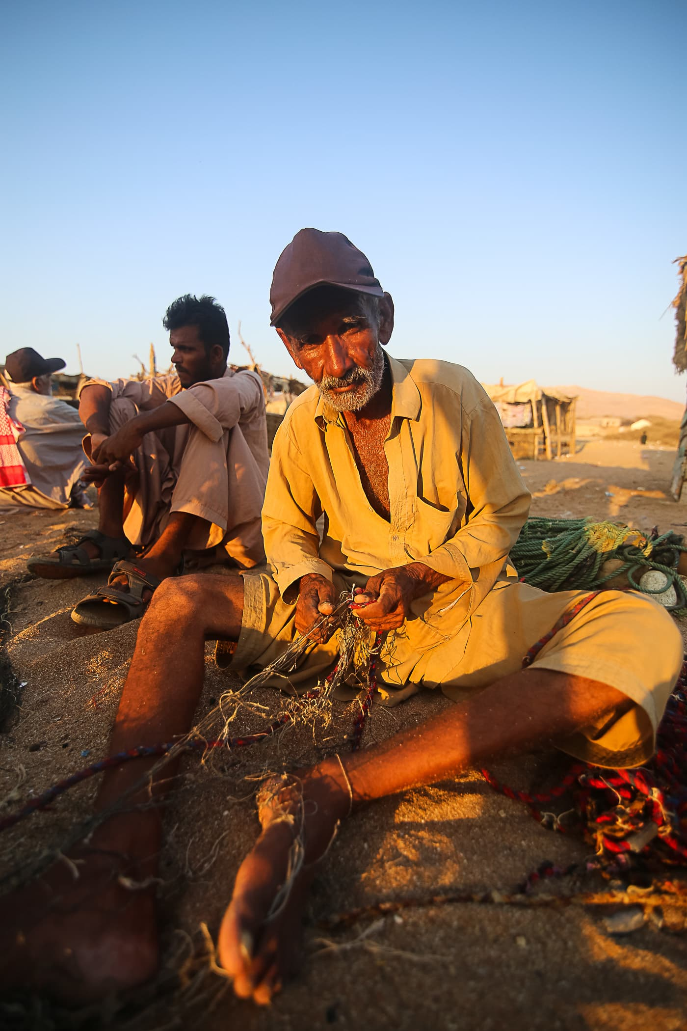 Sitting in the golden light of the setting sun, Chacha Majeed repairs old and damaged nets.