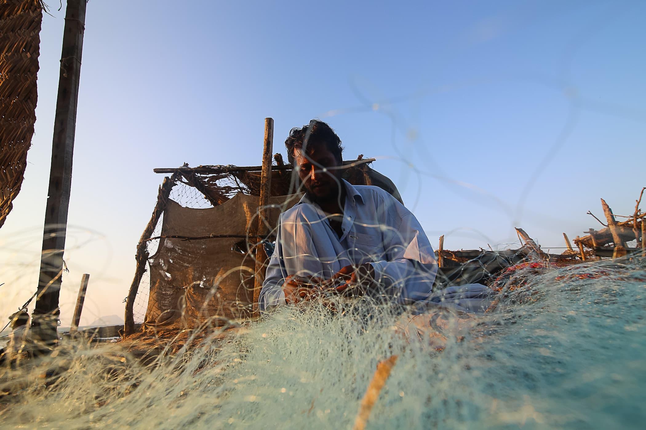 Qasim fixes a new net on the beach at Mubarak Village.