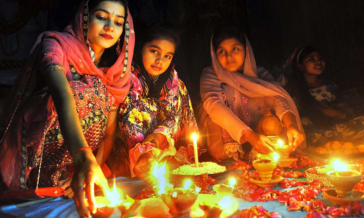 Hindu girls busy in their religious rituals during Diwali Festival in Shiva Mandir at Thandi Sarak. —APP