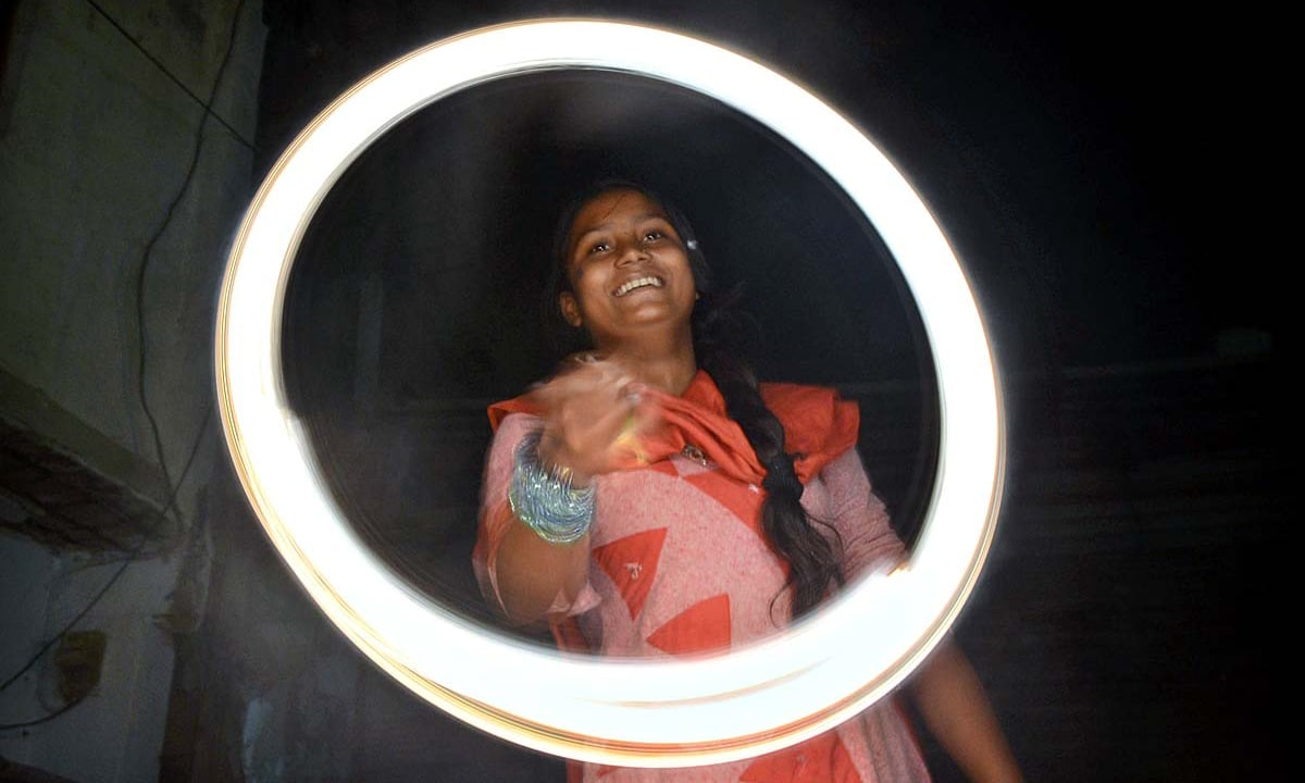 Hindu girl plays with fireworks to celebrate Diwali at Hindu Colony Shree Swami Narayan Temple. —APP