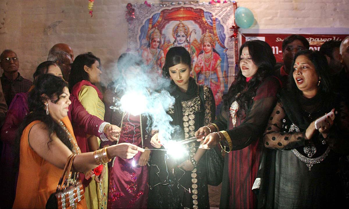 Hindu women play with fireworks to celebrate Diwali Festival at Balmic Mandir. —APP